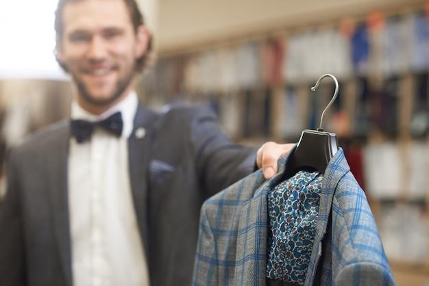 Elegante man in kostuum met strikje in mannelijke winkel.