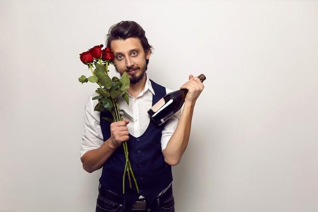 Elegante man met een baard en bril op valentijnsdag in een wit overhemd en vest op een witte muur staat met een boeket rode rozen en een fles champagne