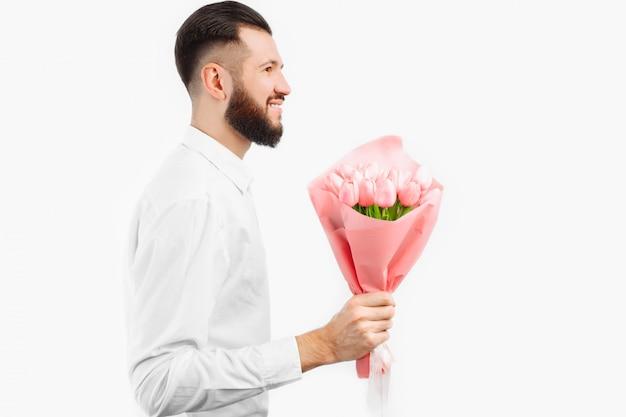 Elegante man met een baard met een boeket tulpen, een geschenk voor valentijnsdag