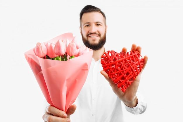 Elegante man met een baard, met een boeket van roze tulpen en een rood valentijn hart, een cadeau voor valentijnsdag