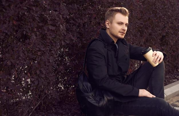 Elegante man poseren in zwart pak