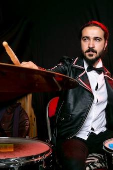 Elegante man spelen op cimbaal met stokken