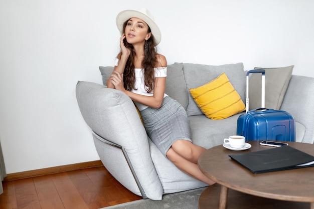 Elegante meisje in een hoed kijkt dromerig in de verte zittend op een bank in een hotel. een reiziger bestelde koffie, naast haar staat haar blauwe bagage
