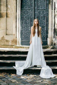 Elegante meisje in lange witte jurk poseren over oude deur