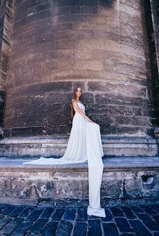 Elegante meisje in lange witte jurk poseren over oude stenen muur