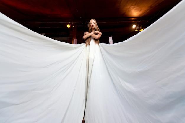 Elegante meisje in lange witte vliegende jurk poseren op de trap binnen