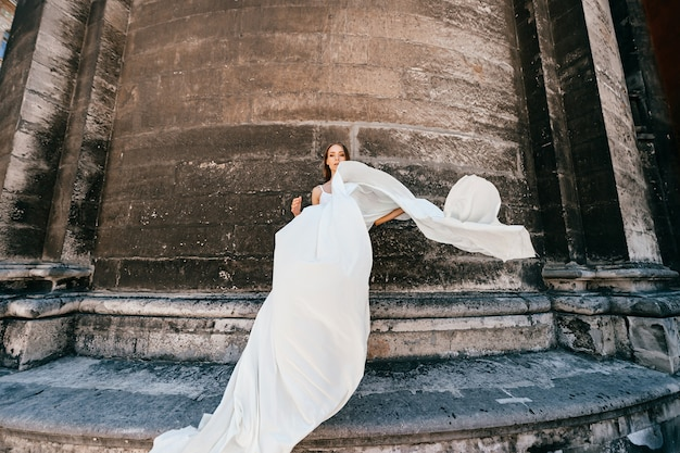 Elegante meisje in lange witte zwierige jurk poseren over oude stenen muur