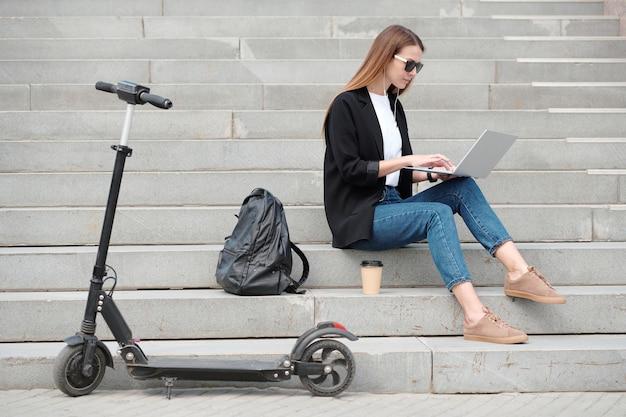 Elegante meisje met laptop surfen in het net op trap met haar rugzak en drankje in de buurt terwijl het hebben van pauze na wandeling op elektrische scooter