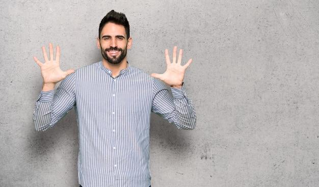Elegante mens met overhemd die tien met vingers over geweven muur tellen