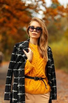 Elegante mode mooie vrouw met stijlvolle zonnebril in vintage gele gebreide trui en zwarte jas wandelingen in de herfst natuur met kleurrijke gouden bladeren
