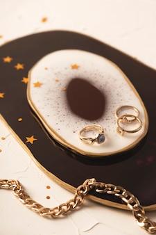 Elegante moderne vrouwelijke sieraden op een prachtige standaard van epoxyhars met abstracte vlekken. luxe trending levensstijl