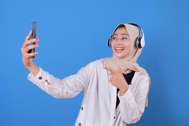 Elegante mooi meisje muziek luisteren terwijl het nemen van foto van zichzelf. enthousiaste vrouw met behulp van telefoon voor selfie