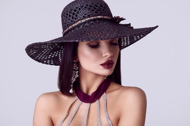 Elegante mooie brunette vrouw in een kleurrijke jurk en brede hoed