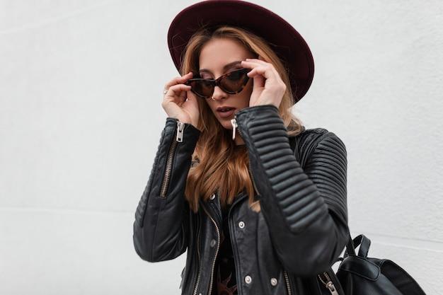 Elegante mooie jonge hipster vrouw in een vintage hoed in stijlvolle zonnebril in een modieuze zwart lederen jas met een rugzak