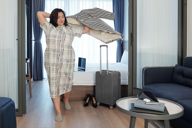 Elegante mooie jonge plus size vrouw die een jas aantrekt en zich klaarmaakt om de hotelkamer te verlaten met een ingepakte koffer