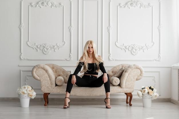 Elegante mooie jonge stijlvolle vrouw in zwarte modieuze kleding met schoenen, zittend op een bank met bloemen in een witte vintage studio