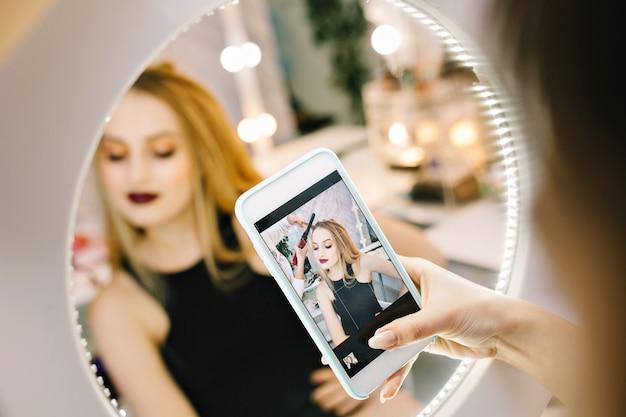 Elegante mooie jonge vrouw foto maken op telefoon in spiegel tijdens het maken van kapsel in de kapsalon. stijlvol modieus model, voorbereid op feest, feest, luxe uitstraling