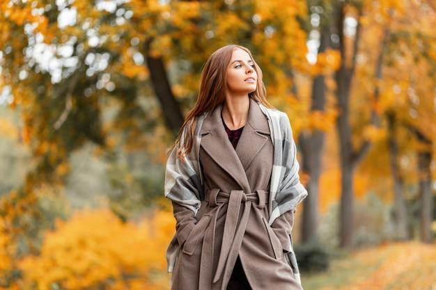 Elegante mooie jonge vrouw in een modieuze lange jas met een stijlvolle gebreide sjaal staat in het park en geniet van het herfstlandschap. trendy meisjesmodel loopt door het bos buiten de stad.