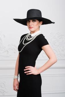 Elegante mooie jonge vrouw in retro-stijl jurk, hoed staande op de lichtgrijze achtergrond.