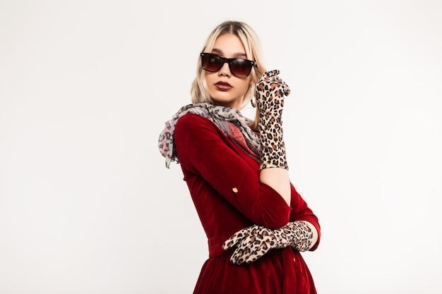 Elegante mooie jonge vrouw met sexy lippen in zonnebril in rode jurk in hoofddoek in luipaardhandschoenen vormt in de buurt van vintage muur. aantrekkelijke glamoureuze meisjesmannequin. trendy dame. retro stijl