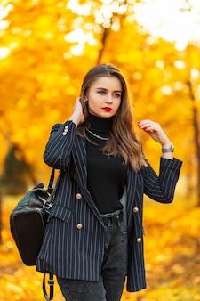 Elegante mooie jonge vrouw model met rode lippen in een modieuze zwarte blazer en trui met een leren rugzak loopt in het park met gele herfstbladeren. zakelijke vrouwelijke stijl buitenshuis