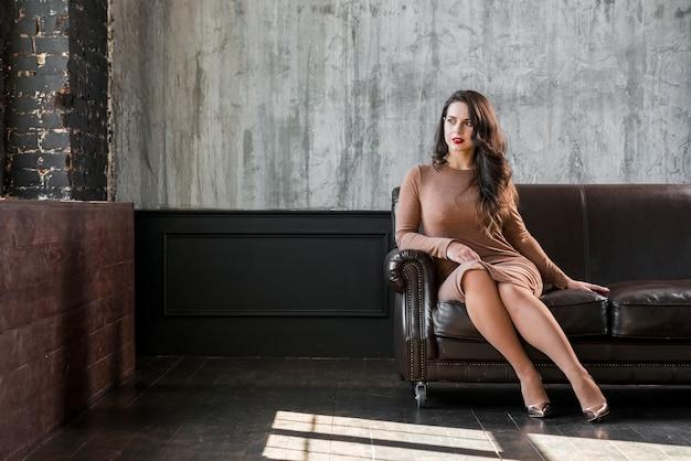 Elegante mooie jonge vrouw zittend op de bank
