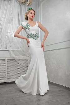 Elegante, mooie, modieuze blonde vrouw in een lange witte dre