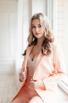 Elegante mooie sexy jonge vrouw in modieus pak en blazer met witte kanten bodysuit in de kamer in de buurt van windows