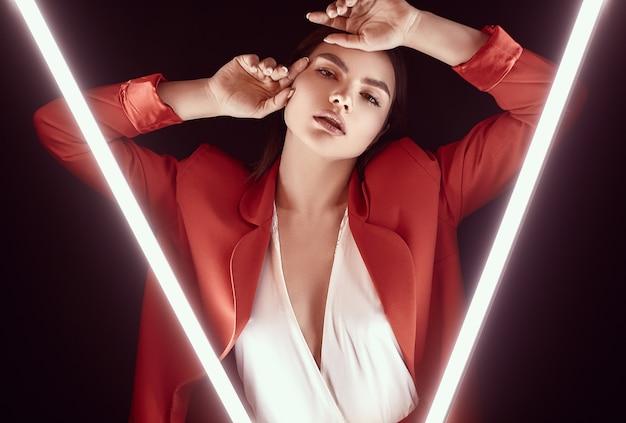 Elegante mooie vrouw in een rode modieuze pak poseren met neonlichten