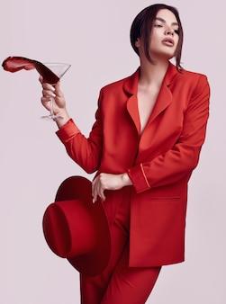 Elegante mooie vrouw in een rood modieus kostuum en hoed met cocktail