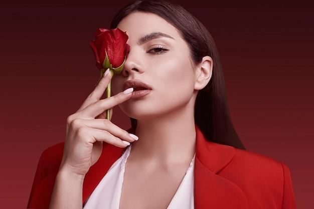 Elegante mooie vrouw in een rood modieus kostuum met roos