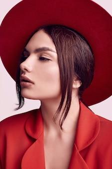 Elegante mooie vrouw in een rood modieus pak en brede hoed