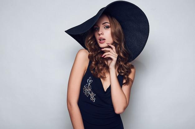 Elegante mooie vrouw in een zwarte jurk en hoed