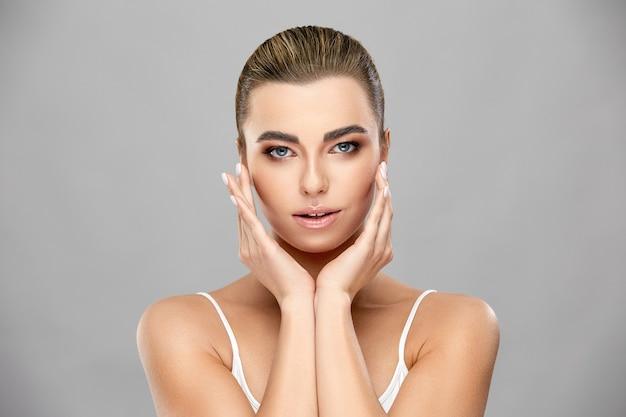 Elegante mooie vrouw met diep grijze ogen en perfecte huid aanraken gezicht met beide armen, beauty concept