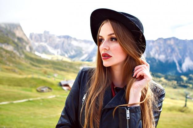 Elegante mooie vrouw met lange haren, trendy hoed en leren jas dragen, poseren in italiaanse dolomieten alpen