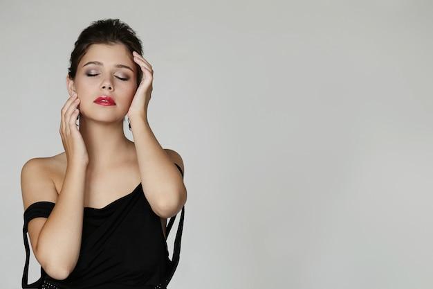 Elegante mooie vrouw poseren met zwarte jurk