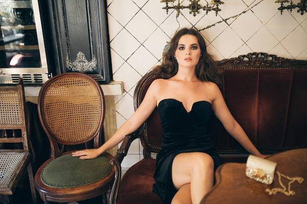 Elegante mooie vrouw zitten in vintage café in zwart fluwelen jurk, avondjurk, rijke stijlvolle dame, elegante modetrend, sexy look