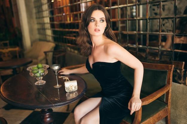 Elegante mooie vrouw zitten in vintage café in zwart fluwelen jurk, avondjurk, rijke stijlvolle dame, elegante modetrend, wachtend op haar vriendje op een date, sensuele look