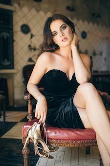 Elegante mooie vrouw zittend op blote voeten in vintage café in zwart fluwelen jurk, avondjurk, rijke stijlvolle dame, elegante modetrend, trok haar schoenen, gouden hoge hakken sandalen, schoeisel uit