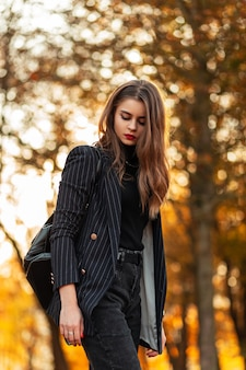 Elegante mooie zakenvrouw met rode lippen in een modieus zwart pak met blazer en een leren rugzak loopt in een park met gele herfstbladeren