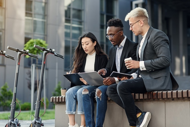 Elegante multiraciale collega's die op de bank in de buurt van kantoor zitten en zakelijke aangelegenheden bespreken