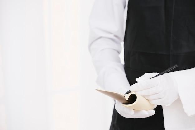 Elegante ober die een notitie schrijft