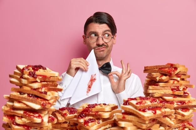 Elegante ober wacht op eerste klant, kijkt opzij, bedachtzame uitdrukking, houdt de hand op de vlinderdas, houdt een vies servet vast, poseert rond sandwiches met jam,