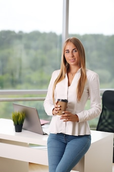 Elegante onderneemster op haar kantoor die een koffiekop houden