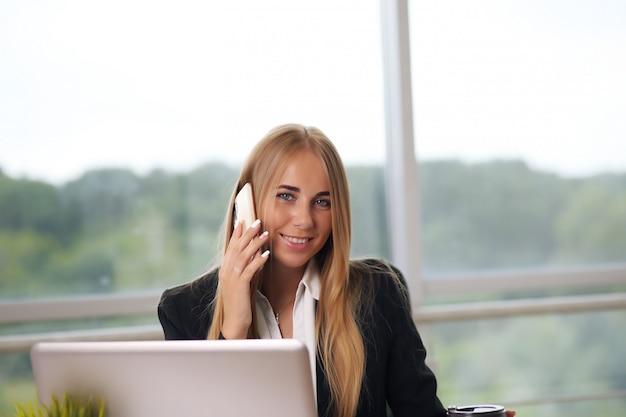 Elegante onderneemsterzitting op haar kantoor en het spreken op de telefoon