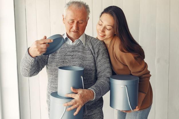 Elegante oude man die thuis staat met zijn kleindochter