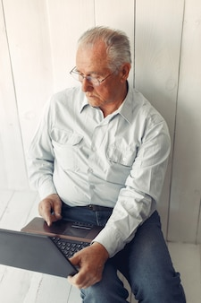 Elegante oude man om thuis te zitten en een laptop te gebruiken