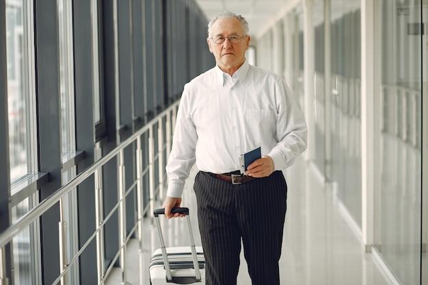 Elegante oude man op de luchthaven met een koffer