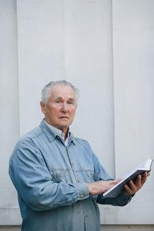 Elegante oude man permanent op grijze achtergrond met een boek