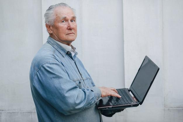 Elegante oude mens die zich op grijze achtergrond bevindt en laptop met behulp van